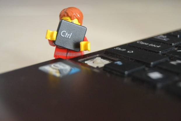 Lego worker holding a CTRL key detached from a laptop keyboard